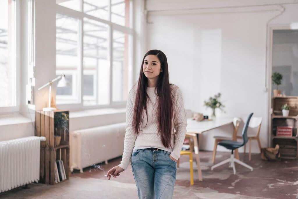Junge Frau steht in einem Raum mit einer Zigarette in der Hand.
