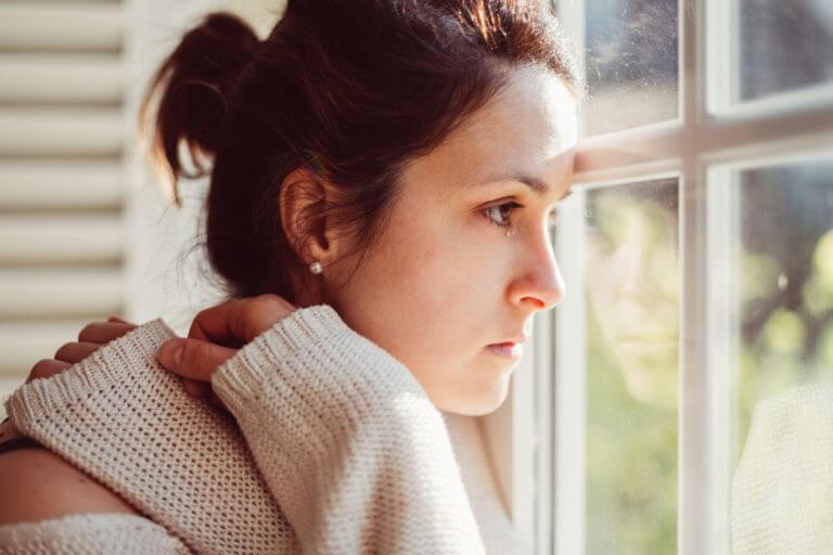 Junge Frau schaut nachdenklich aus einem Fenster.