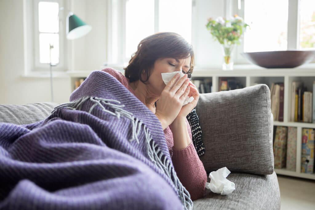 Eine Frau liegt erkältet auf einem Sofa und putzt sich die Nase.