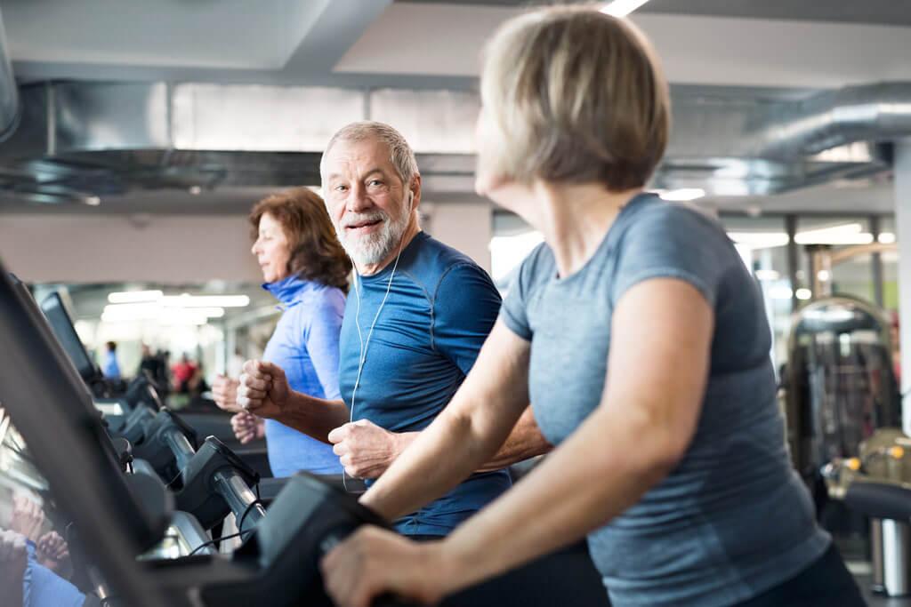 Ein älterer Mann lauft auf einem Laufband in einem Fitnessstudio.