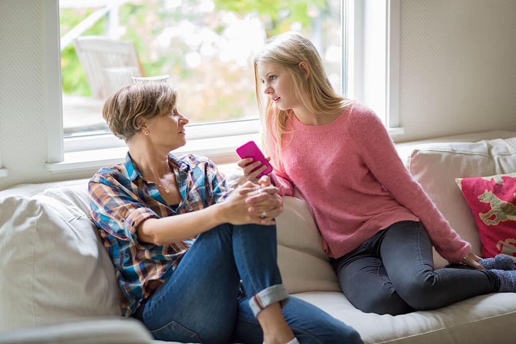 Eine Mutter sitzt mit Ihrer Tochter auf einem Sofa.