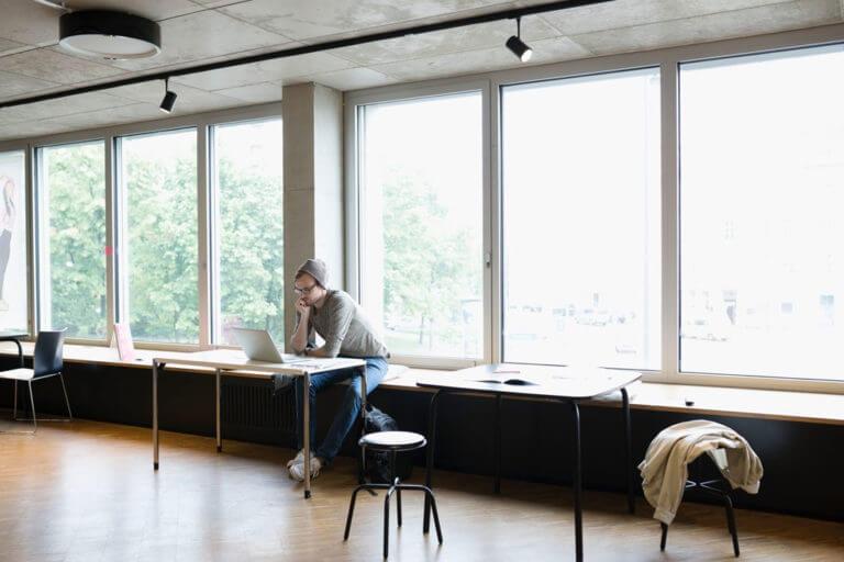 Ein Mann sitzt an einem Tisch und schaut konzentriert auf seinen Laptop.