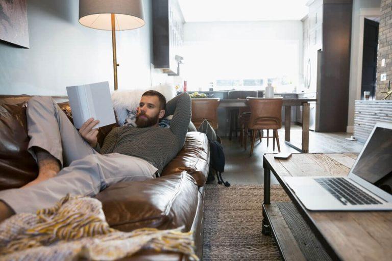 Ein Mann liegt entspannt auf einem Sofa und liest ein Buch.