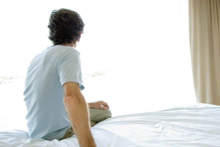 Ein Mann sitzt auf einem Bett und schaut aus einem Fenster.
