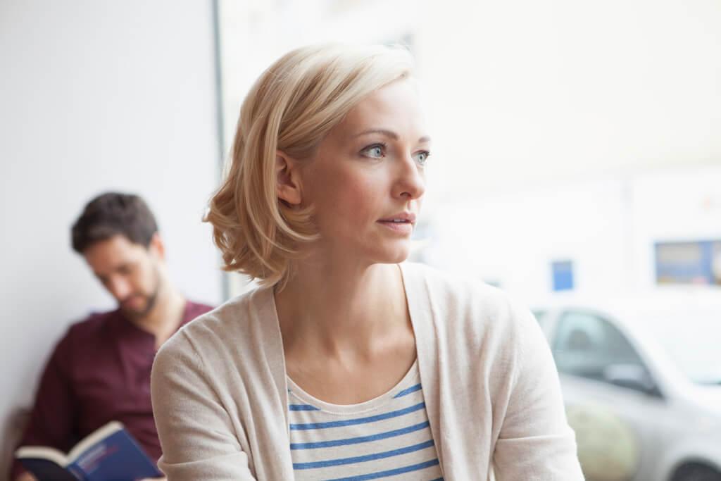 Eine Frau schaut nachdenklich aus einem Fenster.