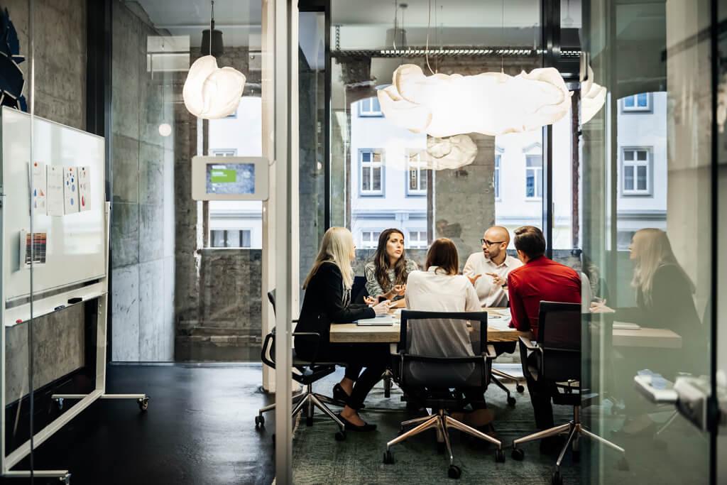 Mehrere Personen sitzen an einem Tisch und besprechen etwas.
