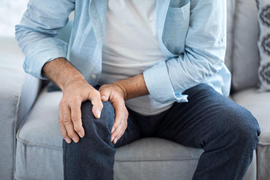 Mann hält sich das Knie vor Schmerz