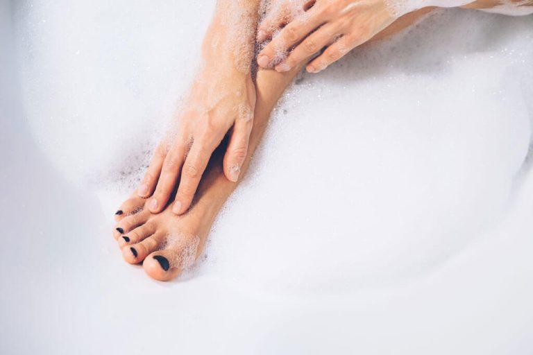 Frau pflegt ihre Füße in der Badewanne