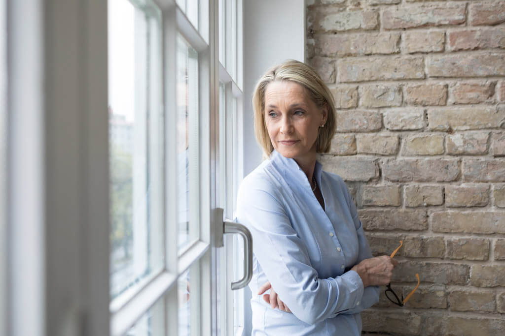 Frau sieht nachdenklich aus dem Fenster