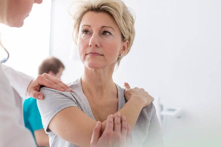 Frau hält sich den Arm und wird vom Arzt behandelt