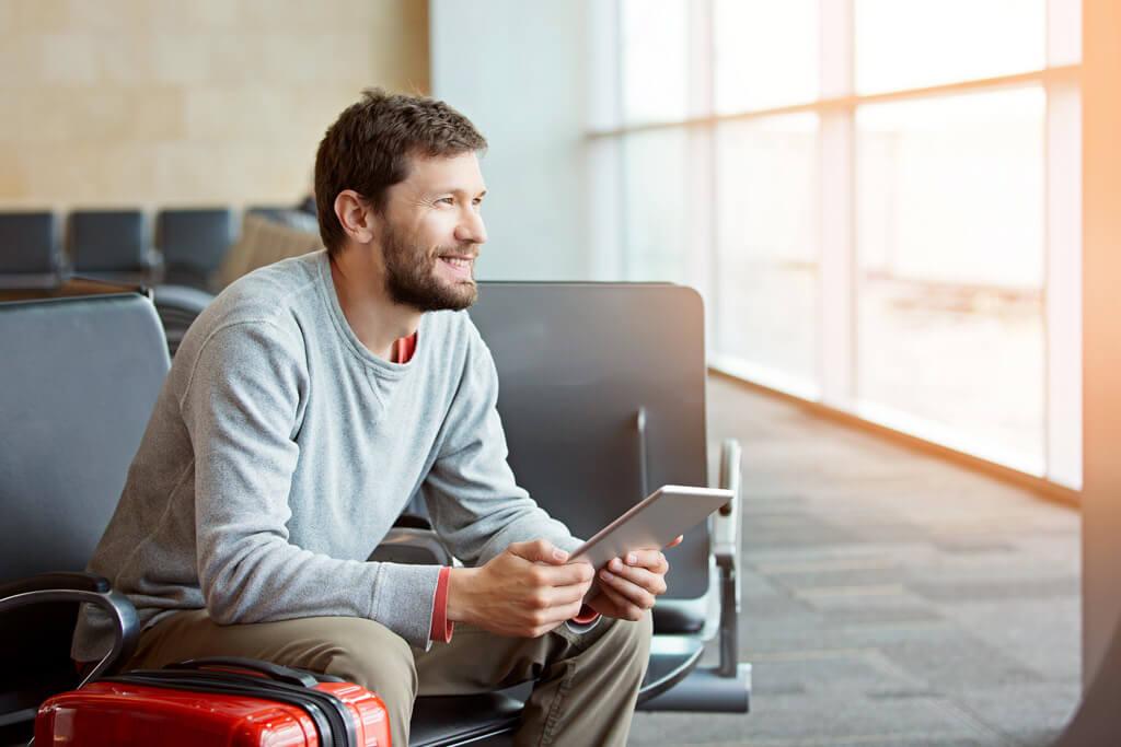 Ein Mann sitzt und wartet am Flughafen.