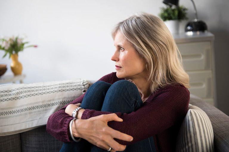 Eine Frau sitzt auf dem Sofa, schaut sehr nachdenklich und umklammert ihre Beine.
