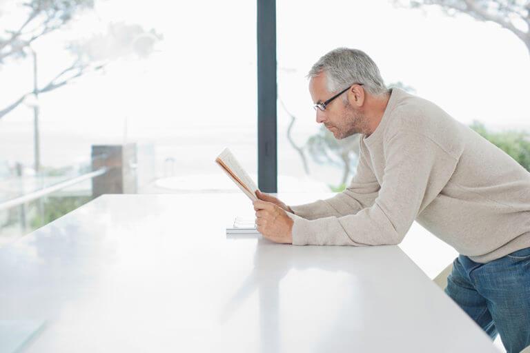 Ein Mann beugt sich über den Küchenthresen und liest eine Zeitschrift.