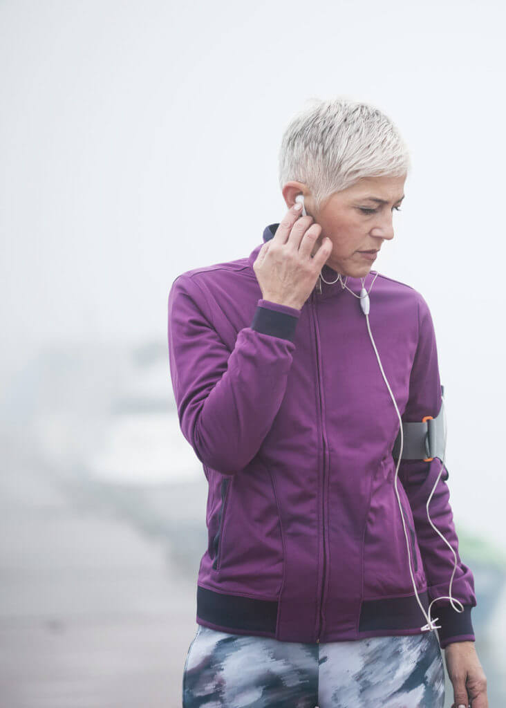 Eine Frau beim Sport steckt sich ihren Kopfhörer ins Ohr