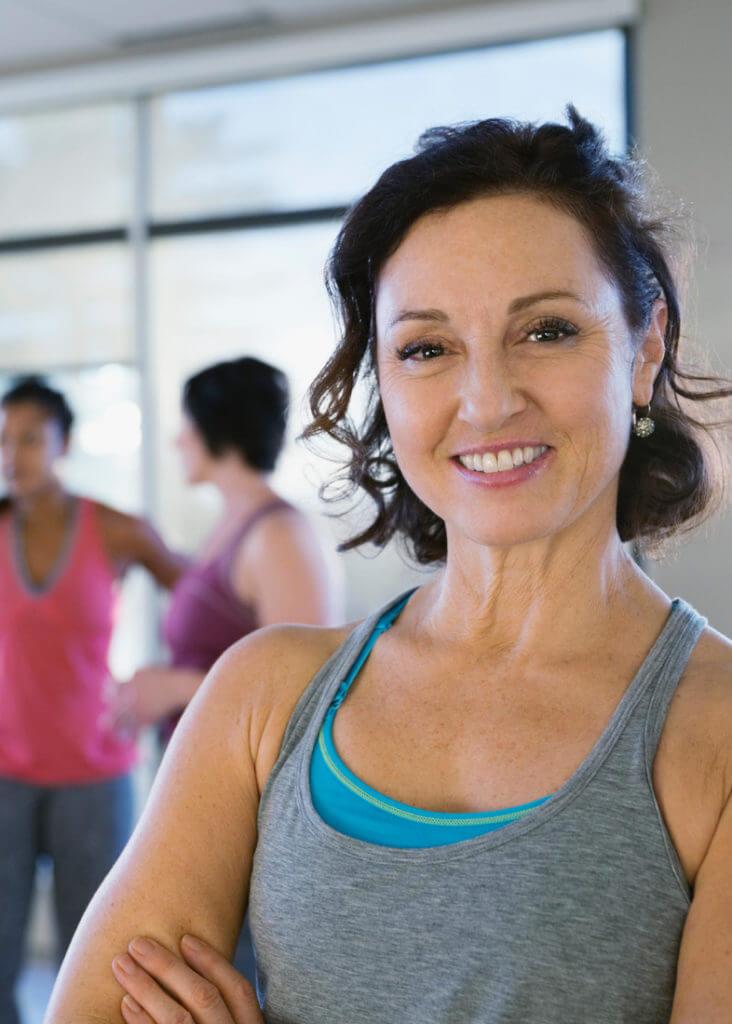 Eine Frau lächelt in einer Sportgruppe