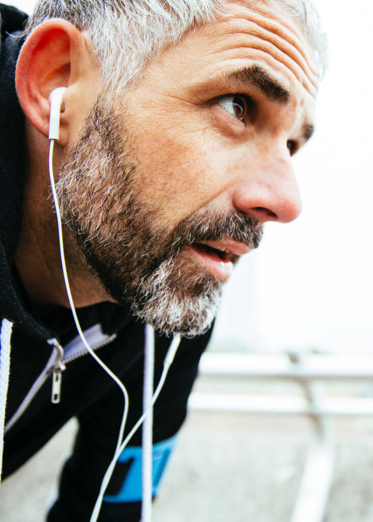 Ein Mann mit Kopfhörern macht eine Pause beim Sport