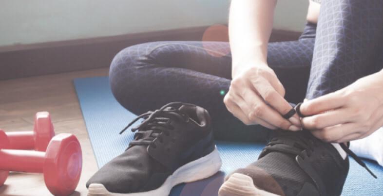 Eine Frau sitzt auf einer Yogamatte und bindet sich ihren Schuh