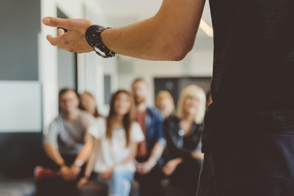 Eine Gruppe hört bei einer Veranstaltung dem Sprecher zu.