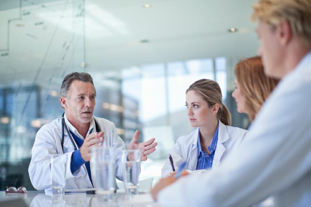 Vier Ärzte sitzen an einem Tisch und besprechen sich über neue Forschungsergebnisse.