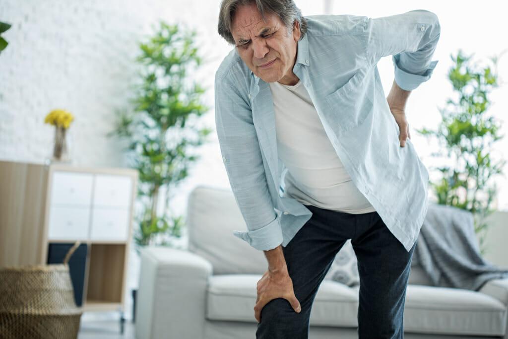 Ein Mann mit schmerzverzerrtem Gesicht hält sich den Rücken mit einer Hand.