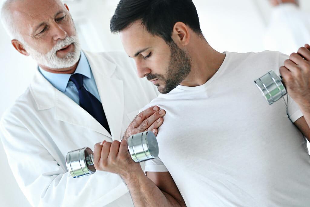 Ein Arzt hilft einem Mann bei der richtigen Ausführung einer Sportübung