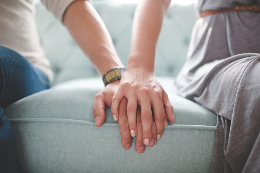 Ein Paar sitzt auf dem Sofa und legen dabei ihre Hände übereinander