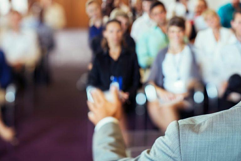 Ein Redner hält einen Vortrag vor einem Saal voller Menschen.