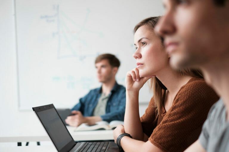 Drei junge Menschen hören aufmerksam einem Vortrag zu
