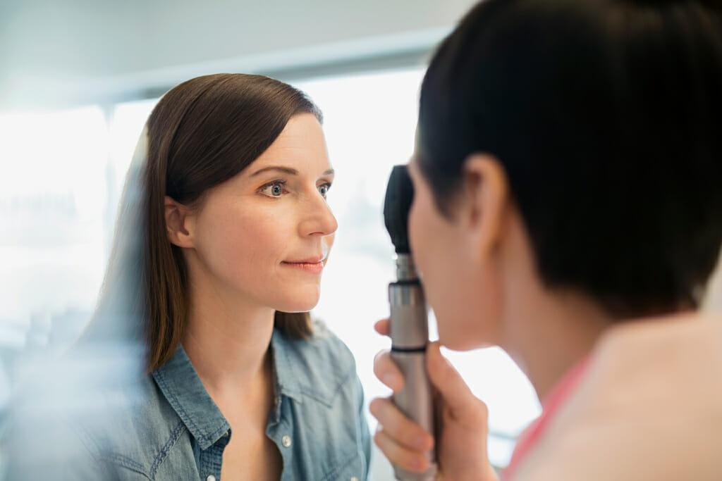 Eine junge Frau lasst sich die Augen untersuchen