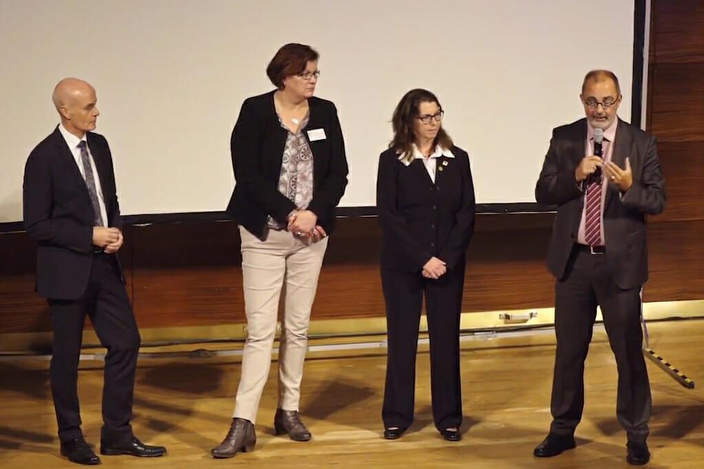 Vier Referenten stehen auf der Bühne, einer von Ihnen hat ein Mikrofon in der Hand.
