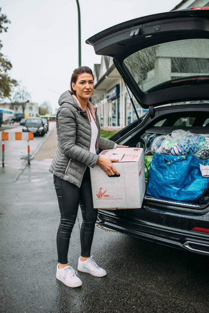 Germaine steht mit einem Umzugskarton vor Ihrem gepackten Auto.