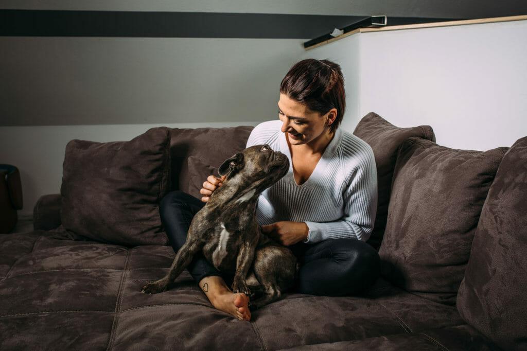 Germaine sitzt mit Ihrem hund auf dem Sofa.
