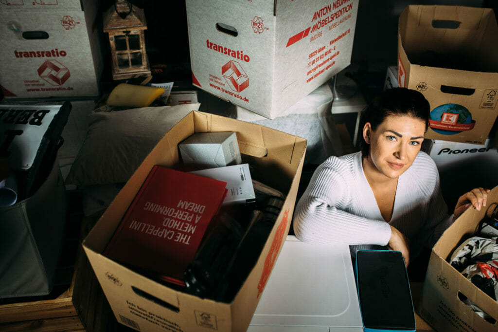 Germaine sitzt zwischen gepackten Umzugskartons.
