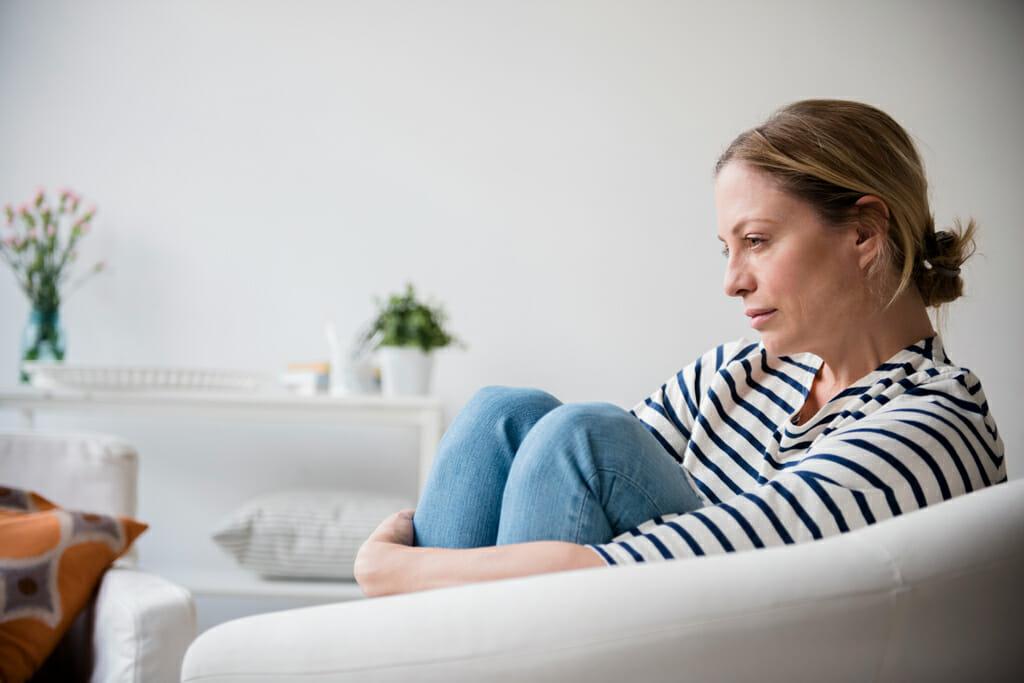 Eine Frau sitzt auf dem Sofa und umklammert Ihre Beine mit einem traurigen Blick