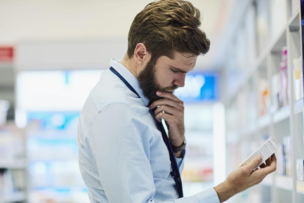 Ein Mann schaut sich die Verpackung eines Medikaments an