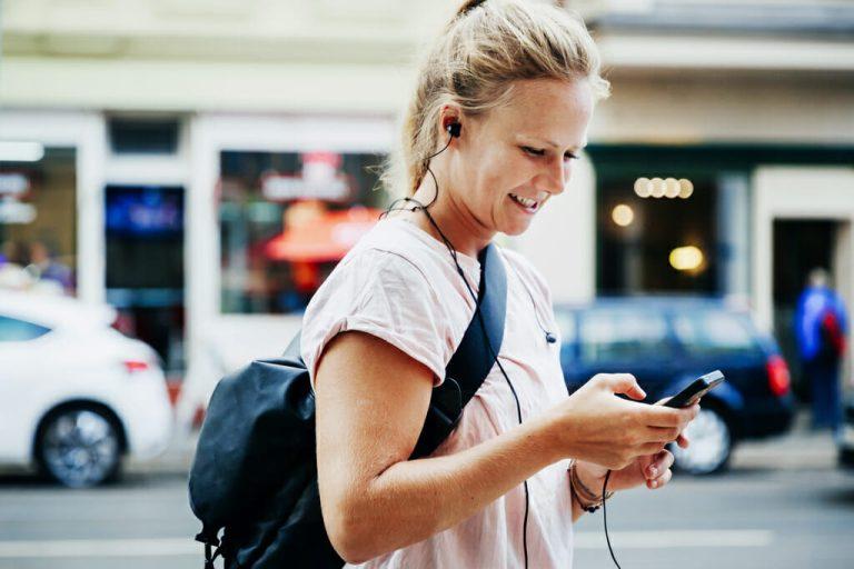 Eine Frau mit einem Rucksack auf dem Rücken schaut auf Ihr Smartphone.