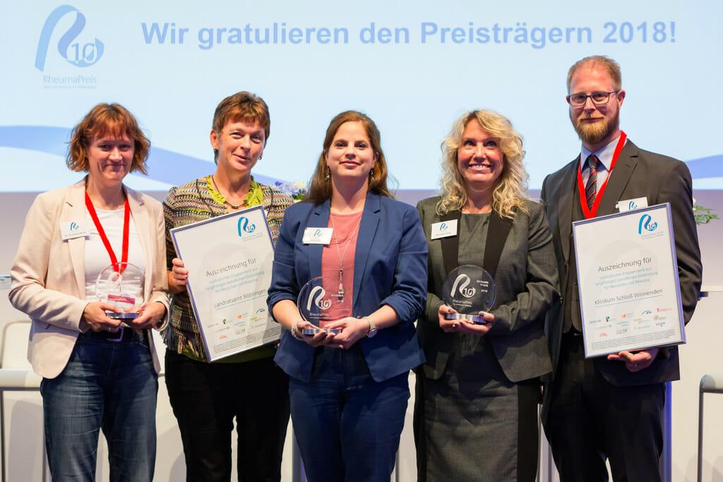 Die Preisträger des RheumaPreises 2018 stehen gemeinsam auf der Bühne.