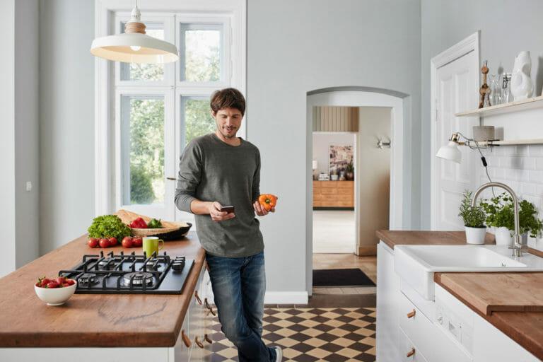Ein Mann steht in der Küche und scaut auf seinem Handy nach einem Rezept.