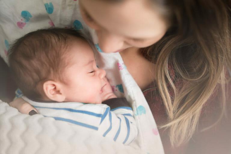 Eine Mutter hält Ihr Baby, in einem Tuch gewickelt, in den Händen.