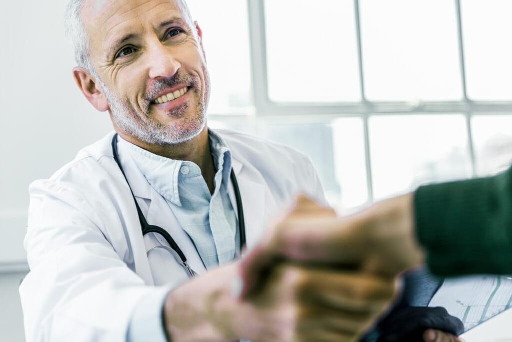 Ein Hautarzt reicht seinem Patienten die Hand