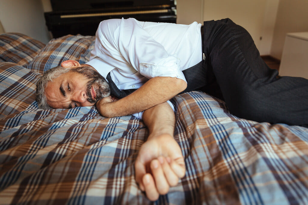 Ein Mann liegt erschöpft auf dem Bett