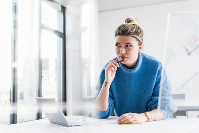 Eine Frau sitzt konzentriert vor Ihrem Laptop.