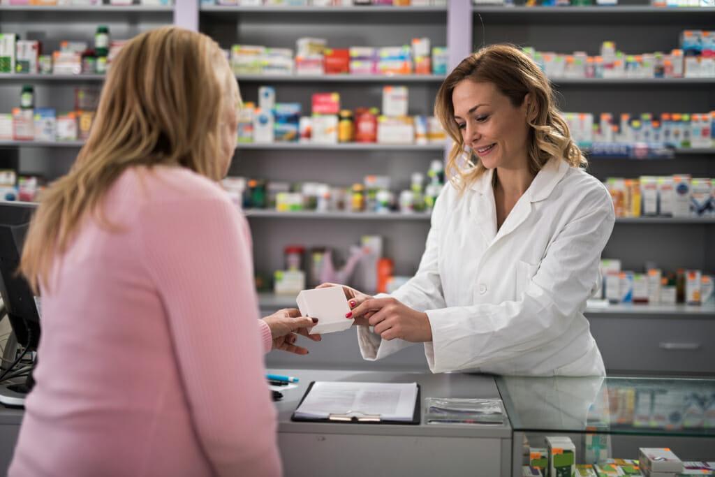 Eine Apothekerin überreicht der Kundin ein Medikament.
