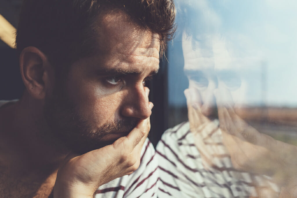 Ein Mann blickt kritisch aus dem Fenster