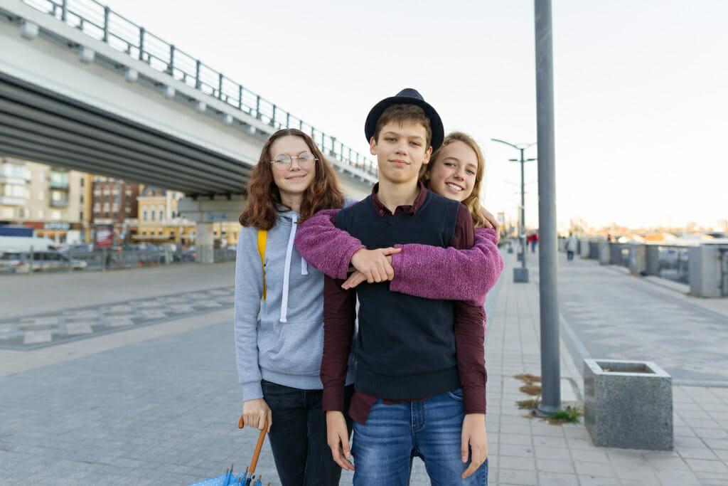 Drei Jugendliche stehen vor einer Brücke.