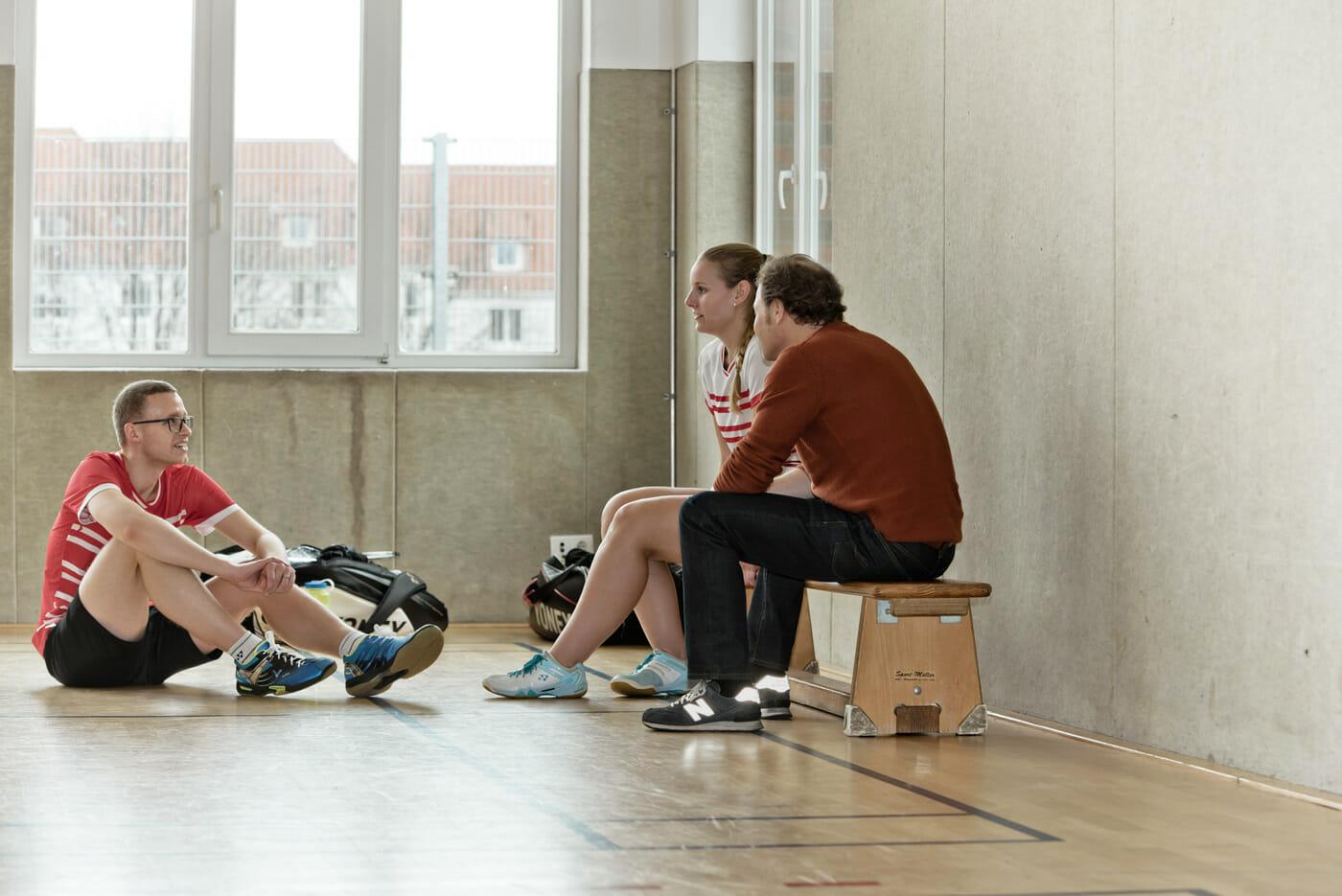 Inken sitzt auf einer Bank in der Turnhalle und unterhält sich