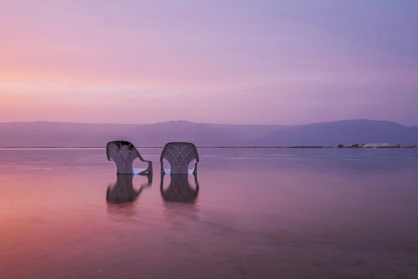 Zwei Stühle stehen am Strand im Wasser