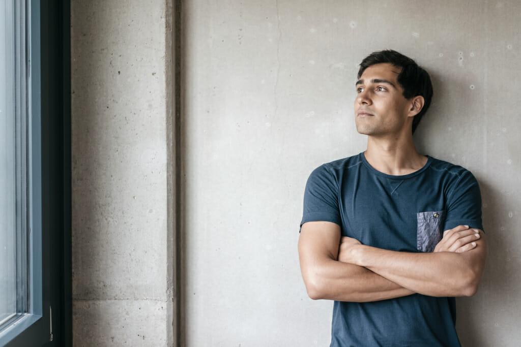 Ein junger Mann lehnt sich an eine Wand an und blickt hinaus.