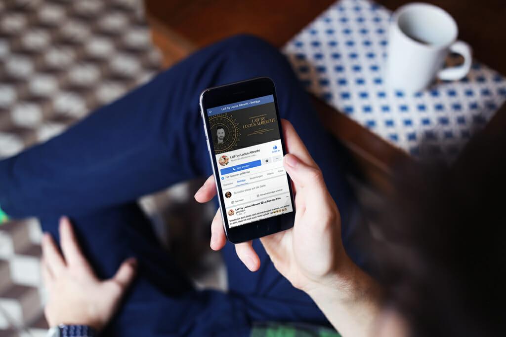 Mann im Cafe browst durch sein Handy