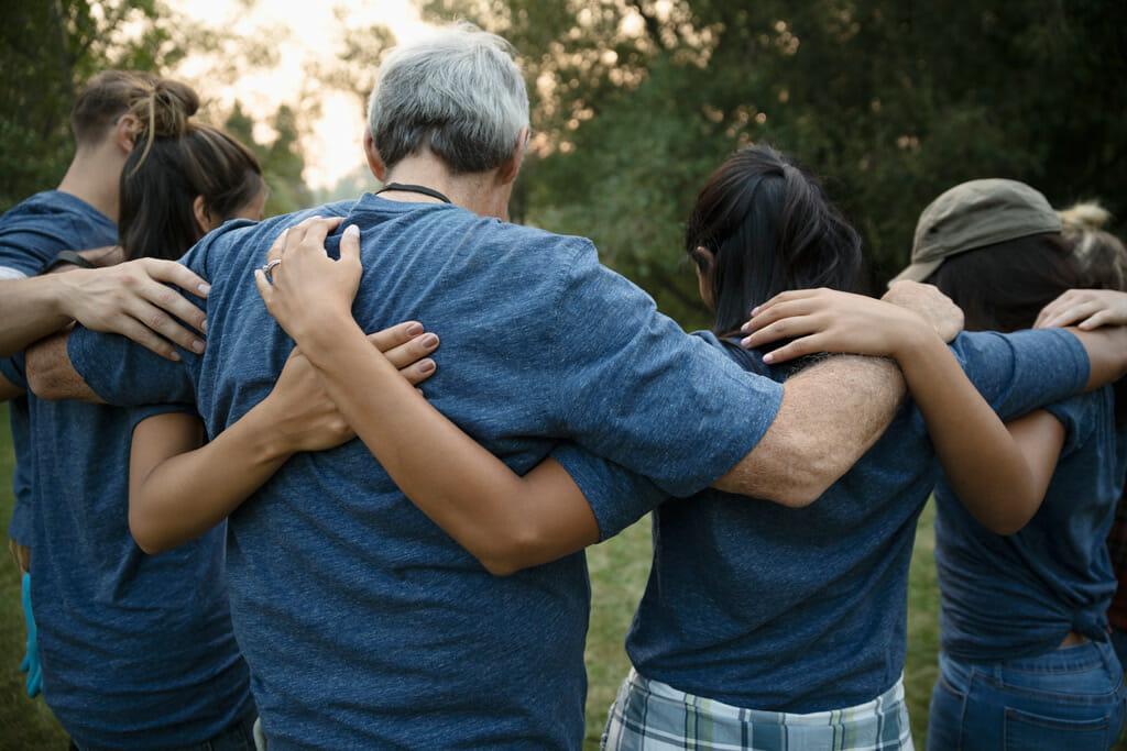 Menschen legen sich die Arme über die Schulter